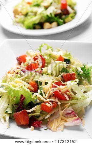 Tasty salmon salad on wooden table background
