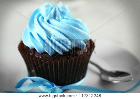 Delicious chocolate cupcake with blue cream on decorated wooden  table, close up
