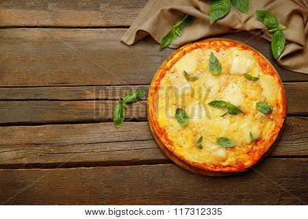 Tasty pizza decorated with basil and cotton napkin on wooden background