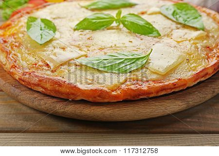 Tasty pizza decorated with basil and vegetables on wooden background, close up