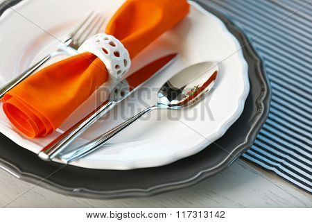 Served table with orange napkin in restaurant, closeup