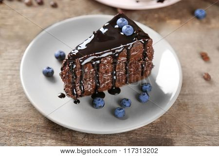 Chocolate cake with chocolate cream and fresh blueberries on plate, on wooden background
