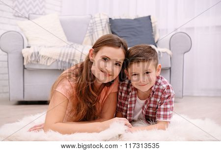 Mother and son lying on the carpet beside sofa in the room
