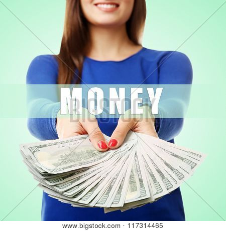 Woman holding money on green background