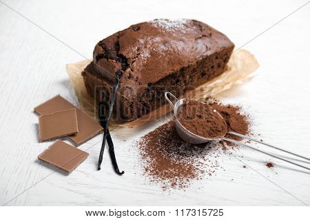 Chocolate cake with cocoa powder, vanilla pods on white table