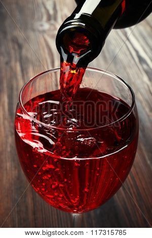 Pouring red wine on wooden background
