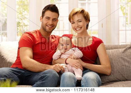 Happy young married couple holding baby girl on lap, smiling, looking at camera.