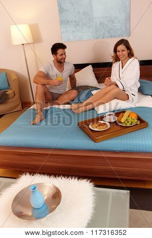 Happy couple having breakfast in the morning in bed, smiling.