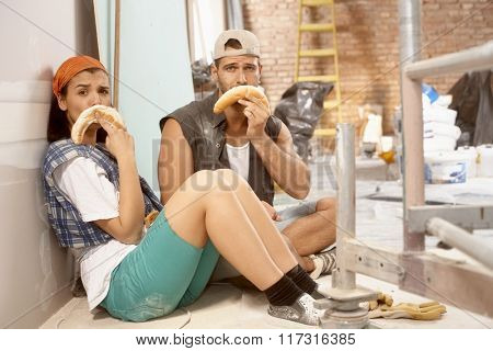 Young couple sitting on floor after daily work on renovating home, making sad face from crescent roll.