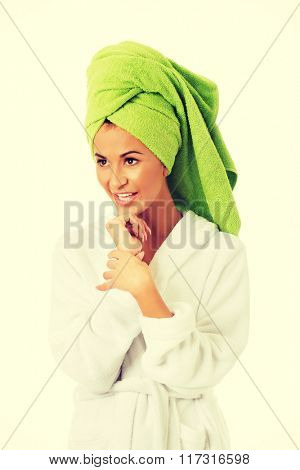 Woman in bathrobe touching chin