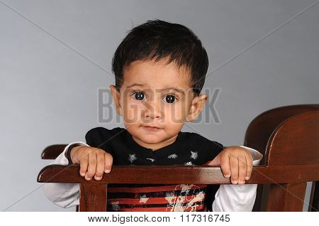 One year old baby sitting on an antique chair