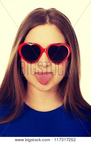 Teen woman in sunglasses shows tongue.