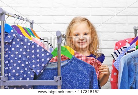 Little girl trying on new clothes