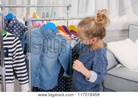 Little girl trying on a new jeans t-shirt