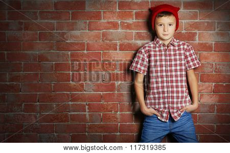 Cute little boy on brick wall background. Kids fashion concept