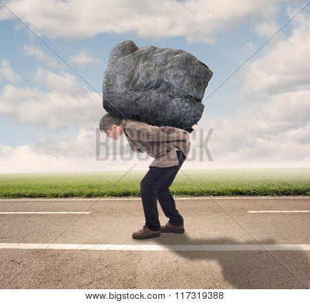 businessman holding a big rock on a road