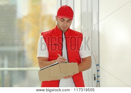 Delivery man in red uniform holding package