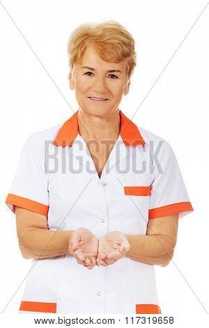 Smile elderly female doctor or nurse presenting something on open palms