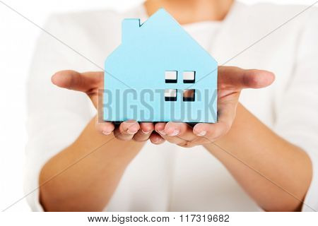 Businesswoman holding a blue paper house