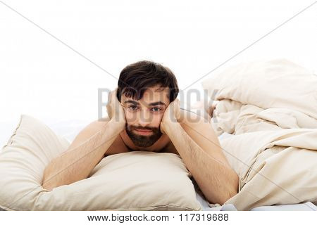 Depressed man in bedroom.
