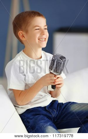 Little boy singing into the microphone on a sofa at home