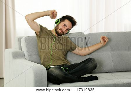 Young man listens music with headphones sitting on grey sofa in the room