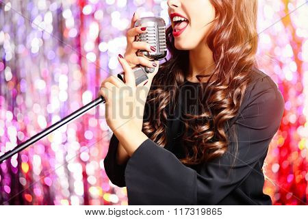 Young singing woman with retro microphone against bright colourful background, close up