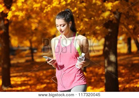 Young beautiful woman with bottle of water running in autumn park and listening to music with headphones.