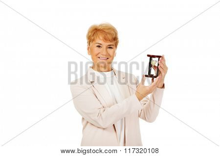 Smile elderly  business woman holding sandglass