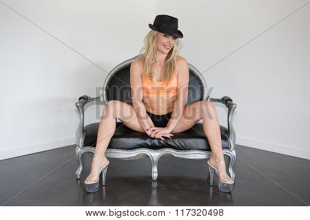 Blond And  Sexy Woman With A Hat Sitting On  Sofa