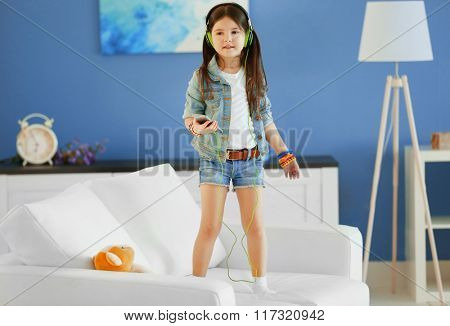 Cute little girl listening music and singing in the room