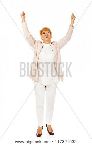 Happy elderly business woman with arms up