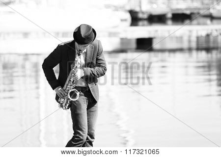 Young man playing on saxophone on the riverside