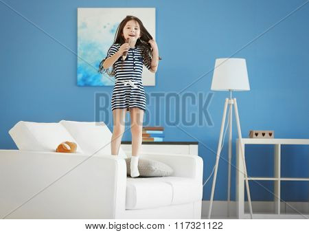 Cute little girl singing in a wooden pencil and has fun in the modern room