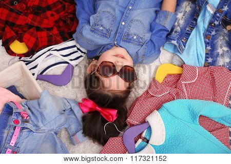 Little girl and a lot of new clothes, top view