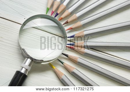 magnifying glass, pencils on wooden table. Copy space for text. Search idea concept