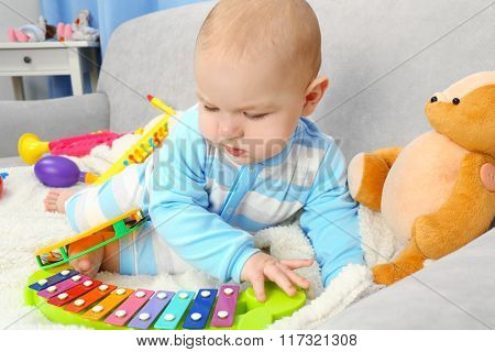 Adorable baby with colourful musical toys on sofa in the room, close up