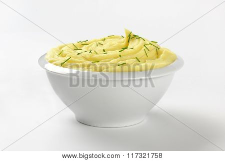 bowl of mashed potato puree with chopped chives on white background