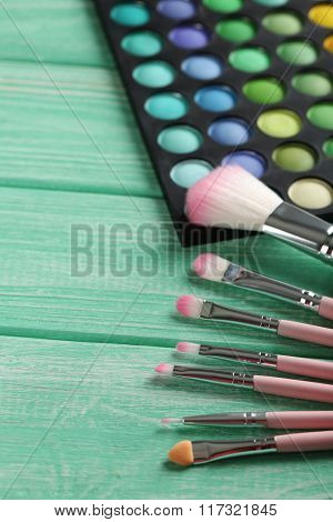 Makeup Brush Set With Palette On A Mint Wooden Table