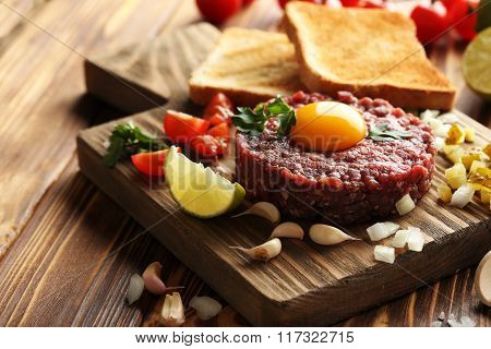 Beef Tartare With Egg Yolk On A Brown Wooden Table