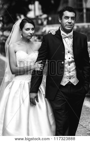 Happy Confident Handsome Groom And Beautiful Emotional Bride Walking In Street B&w