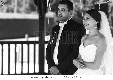 Happy Handsome Groom And Beautiful Bride In White Dress In Wedding Arbor At Ceremony B&w