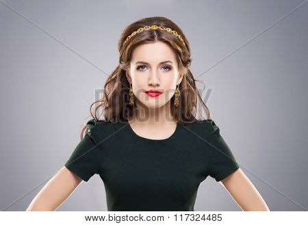 Beautiful, young brunette posing with golden headband and earrings over isolated background.