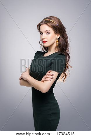 Confident, beautiful, young woman posing over isolated background with golden luxury crown and earrings.