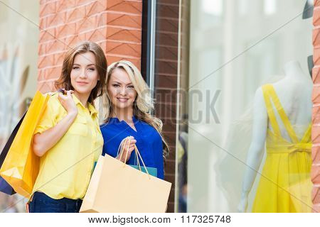 Two attractive sexy shopaholics posing near store window with yellow dress.