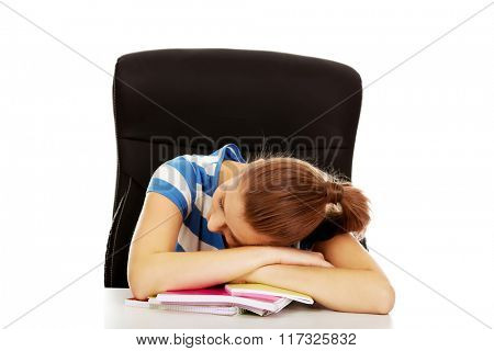 Tired teenage woman sleeping on desk