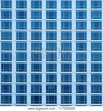 Close-up texture view of blue skyscraper with many windows in Bangkok.