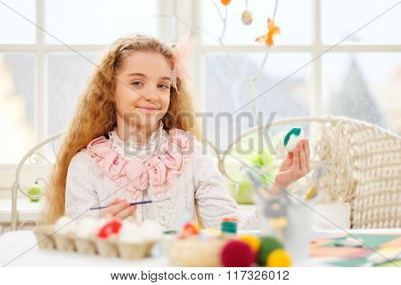 Beautiful young girl decorating Easter eggs at cozy home atmosphere.