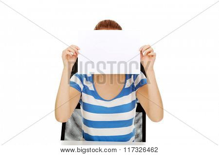 Teenage woman covering face with paper card