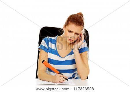 Pensive teenage woman doing homework